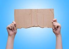 Руки держа пустую часть картона над голубой предпосылкой стоковая фотография