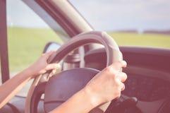 2 руки держа рулевое колесо внутри автомобиля с стоковые изображения