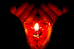 Руки держа свечу горения формы сердца Стоковое Изображение
