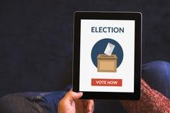 Руки держа цифровой планшет с онлайн голосуя концепцией Стоковое фото RF