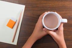 Руки держа чашку горячего питья и неподвижное на таблице Стоковое Изображение RF