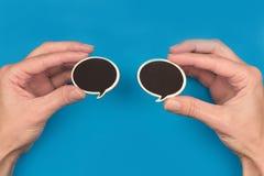 Руки держа 2 черных пузыря речи на голубой предпосылке Стоковая Фотография RF