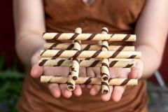 Руки держа waffle свертывают с сливк шоколада Стоковая Фотография RF
