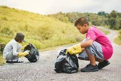 Руки детей в желтых перчатках выбирая вверх пустую пластмассы бутылки в сумку ящика Стоковое фото RF
