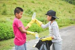 Руки детей в желтых перчатках выбирая вверх пустую пластмассы бутылки в сумку ящика Стоковые Фото