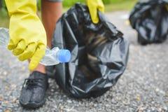 Руки детей в желтых перчатках выбирая вверх пустую пластмассы бутылки в сумку ящика Стоковое Изображение