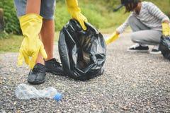 Руки детей в желтых перчатках выбирая вверх пустую plast бутылки Стоковые Фото