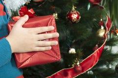 Руки детей держа подарок рождества Стоковые Изображения RF