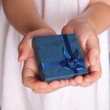 Руки детей держа подарок Стоковое Фото