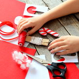 Руки детей на старом деревянном столе Handmade орнамент конфеты рождества войлока, войлок покрывает и утили, ножницы, красный пот Стоковое Фото
