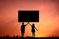 Руки детей силуэта держа знаки Стоковое фото RF