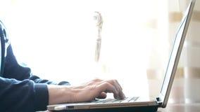 Руки детенышей уменьшают слепую печать человека на компьтер-книжке дома сток-видео