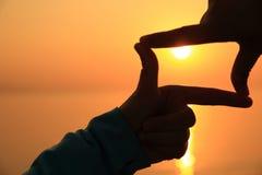 руки делая квадратную форму против яркого захода солнца моря Стоковая Фотография