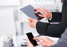 Руки деловых партнеров используя приборы стоковая фотография