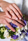 Руки жениха и невеста лежат на букете цветков взгляд сверху венчание стоковые изображения rf