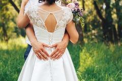 Руки жениха на талии невесты он сердце mades от его рук Стоковое Изображение