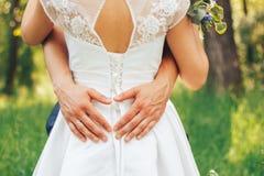 Руки жениха на талии невесты он сердце mades от его рук Стоковые Фото