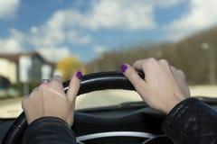 Руки женского водителя на рулевом колесе Стоковое фото RF
