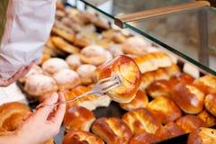 Руки женского работника хлебопекарни пакуя хлеб Стоковое Фото