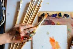 Руки женского художника на грязной пакостной палитре с различной стоковое изображение