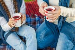 Руки женщина и ребенок держа чай чашки стоковая фотография