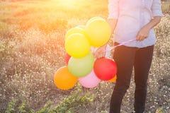 Руки женщины битника держа multi цвет воздушных шаров в mea Стоковое Изображение RF