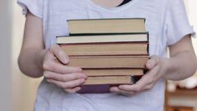 Руки женщины борясь для того чтобы снести кучу книг, конец вверх с малой глубиной поля видеоматериал