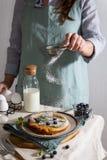 Руки женщины брызгая напудренный сахар на домодельном голландском блинчике младенца с голубиками, мятой и напудренным сахаром вку стоковая фотография rf