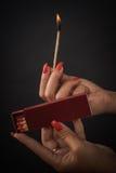 Руки женщины воспламеняют большие спички для сигары или камина Стоковые Фото