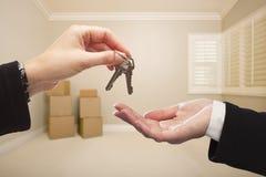Руки женщины вручая над ключами дома внутри пустой комнаты Tan Стоковое фото RF