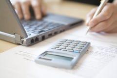 Руки женщины высчитывая домой финансы на столе Стоковое фото RF