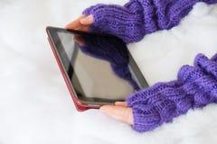 Руки женщины в светлым mittens связанных teal проводят современную плату Стоковые Изображения