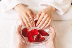 Руки женщины в стеклянном шаре с водой на белом полотенце стоковое изображение