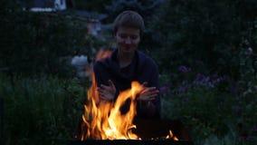 Руки женщины грея около огня акции видеоматериалы