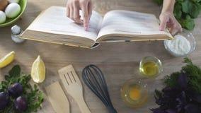 Руки женщины держа варить книгу, девушку выбирая рецепт и слегка ударяя страницы сток-видео