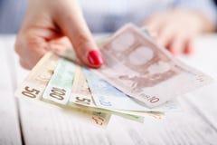 Руки женщины держа деньги Стоковые Изображения