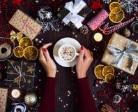 Руки женщины держа кофейную чашку выпивают коробку праздничного подарка рождества на украшенной праздничной таблице Стоковая Фотография