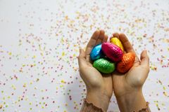 Руки женщины держа красочные пасхальные яйца шоколада с белой предпосылкой и красочный запачканный confetti стоковое изображение
