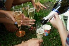 Руки женщины держа красочные стекла и лить шампанское на Стоковая Фотография