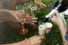 Руки женщины держа красочные стекла и лить шампанское на Стоковые Фото