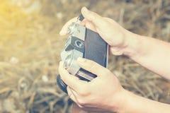 Руки женщины держат старую винтажную камеру фильма outdoors тонизировано стоковое фото