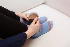 Руки женщины держа горячий напиток, сидя на кресле Стоковое Изображение