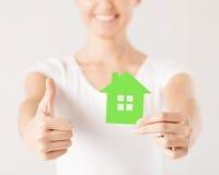 Руки женщины держа зеленый дом Стоковая Фотография