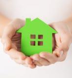 Руки женщины держа зеленый дом Стоковое Фото