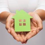 Руки женщины держа зеленый дом Стоковые Фото