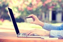 Руки женщины держа кредитную карточку и используя компьютер Стоковые Фото
