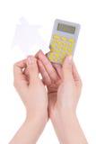 Руки женщины держа дом карманного калькулятора и бумаги изолировали o Стоковая Фотография RF