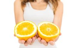 Руки женщины держа половины апельсина Стоковое фото RF