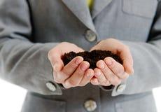 Руки женщины держа пригорошню земли Стоковое Фото