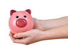 Руки женщины держа розовую копилку Стоковая Фотография RF
